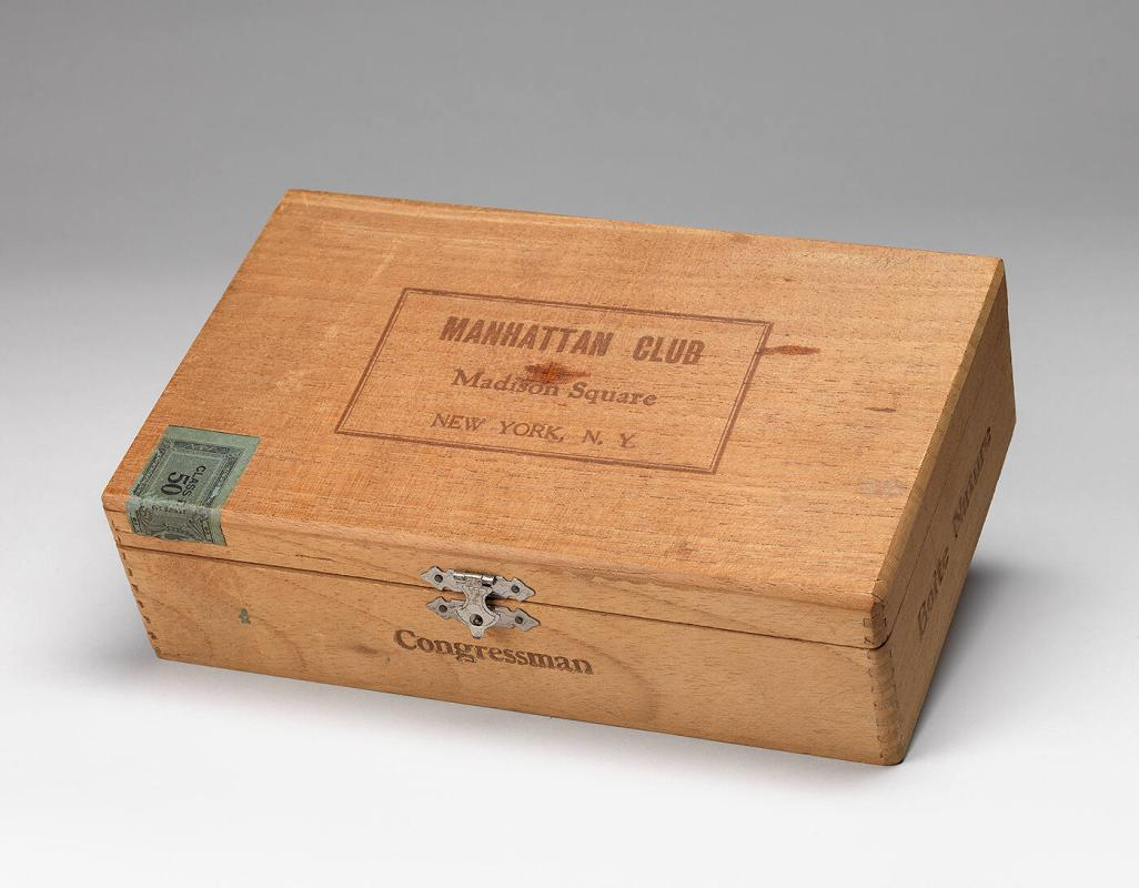 Cedar Cigar Box (Manhattan Club | Madison Square | New York, NY) containing magnifying glass, pen knife, voodoo doll, 2 mailing tags, 2 plates for printing, and small key