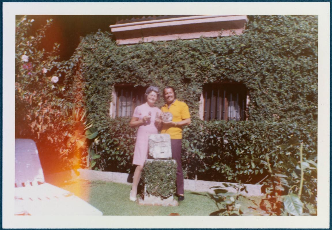 Cuernavaca, Mexico home of Robert Brady, man and woman in yard holding small dog