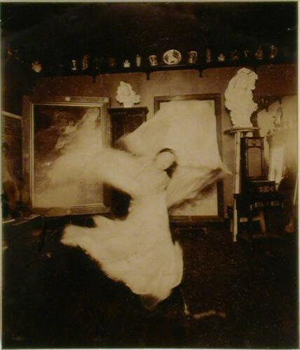 Loïe Fuller practicing at home in front of a Mucha playbill, Passy near Paris