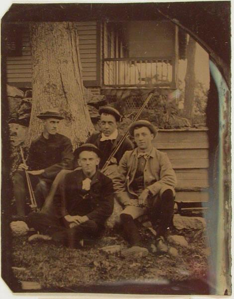 Portrait of four men sitting in front of a house